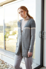 woman wearing a grey knit cardigan with pockets with a dark grey and cream polka dot pattern yoke