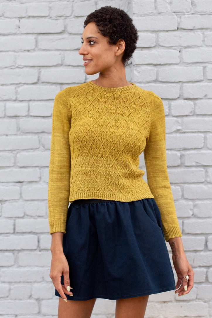 A woman wearing a mustard knit sweater and a navy skirt