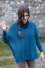 woman wearing a loose fitting cabled v-neck knit sweater in blue