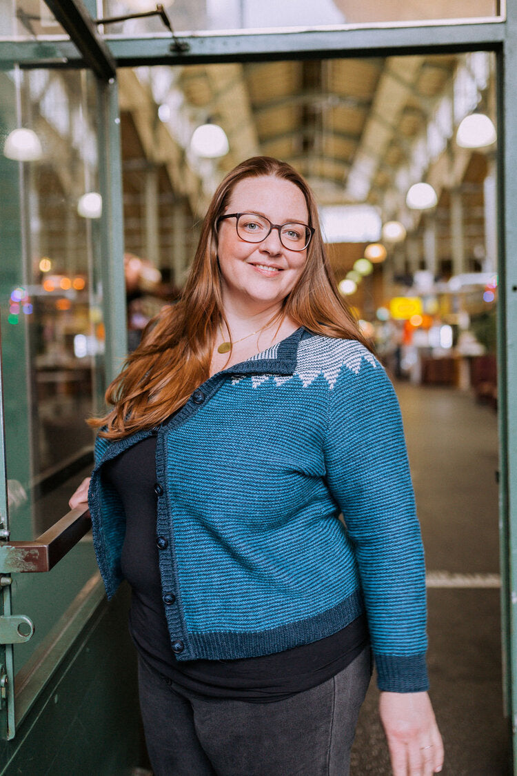 a woman standing in a market wearing a blue knit cardigan with a grey patterened yoke.
