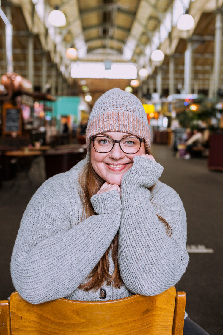 a woman sitting backwards on a chair in a market wearing a grey knit sweater and hat