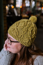 a woman wearing a green hat knit hat with a cable pattern