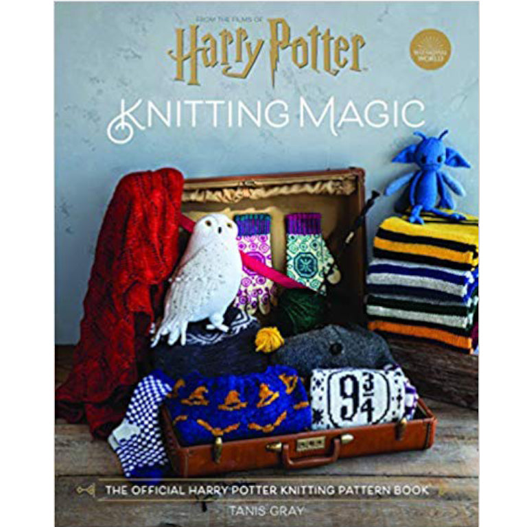 Cover photo of Harry Potter Knitting Magic. A suitcase filled with knits from the book sitting beside a stack of knit house scarves