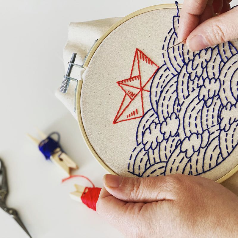 hands working on an embroidery of a paper boat on waves