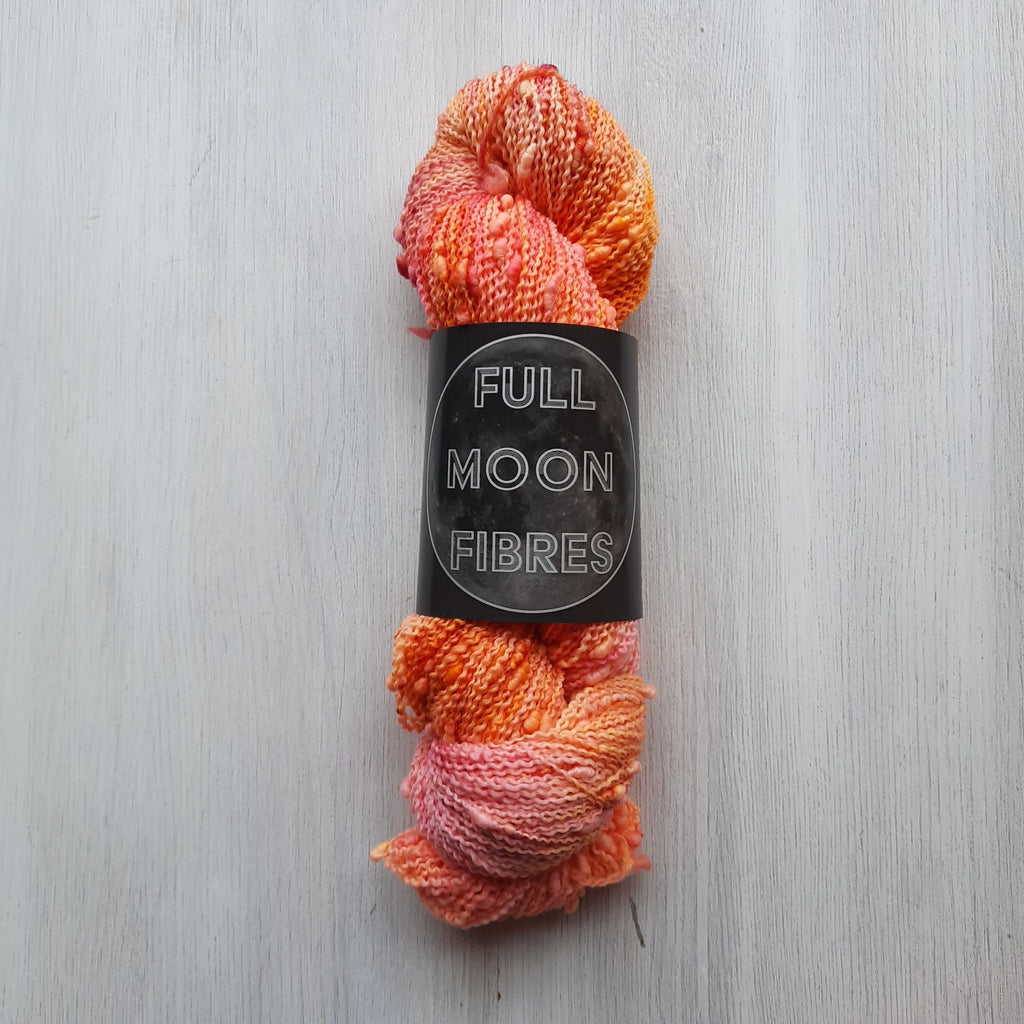 tonal oranges, pink, yellow variegated textured skein of yarn