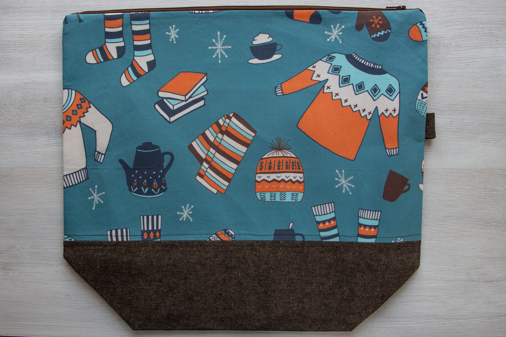 project bag with blue background and print with sweaters, socks, hats, books, and scarves