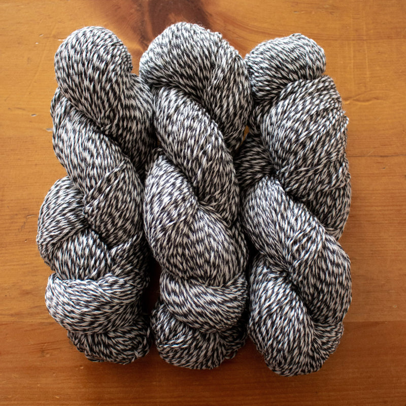 three skeins of marled yarn natural and black