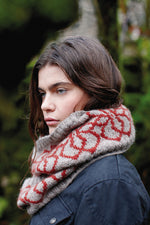 woman wearing a grey knit cowl with a red colourwork flower pattern
