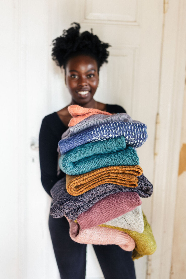 woman holding a pile of many folded knitted garments