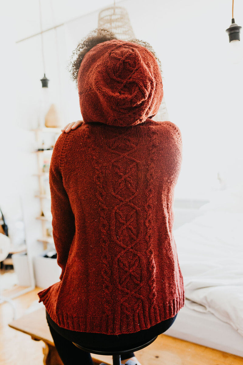 rust coloured knit hoodie with a cable pattern in the centre back