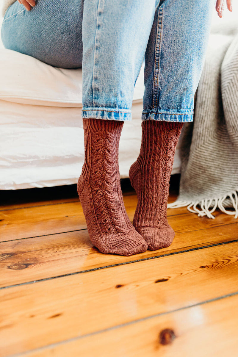 rust coloured socks with a cable pattern up the foot and leg