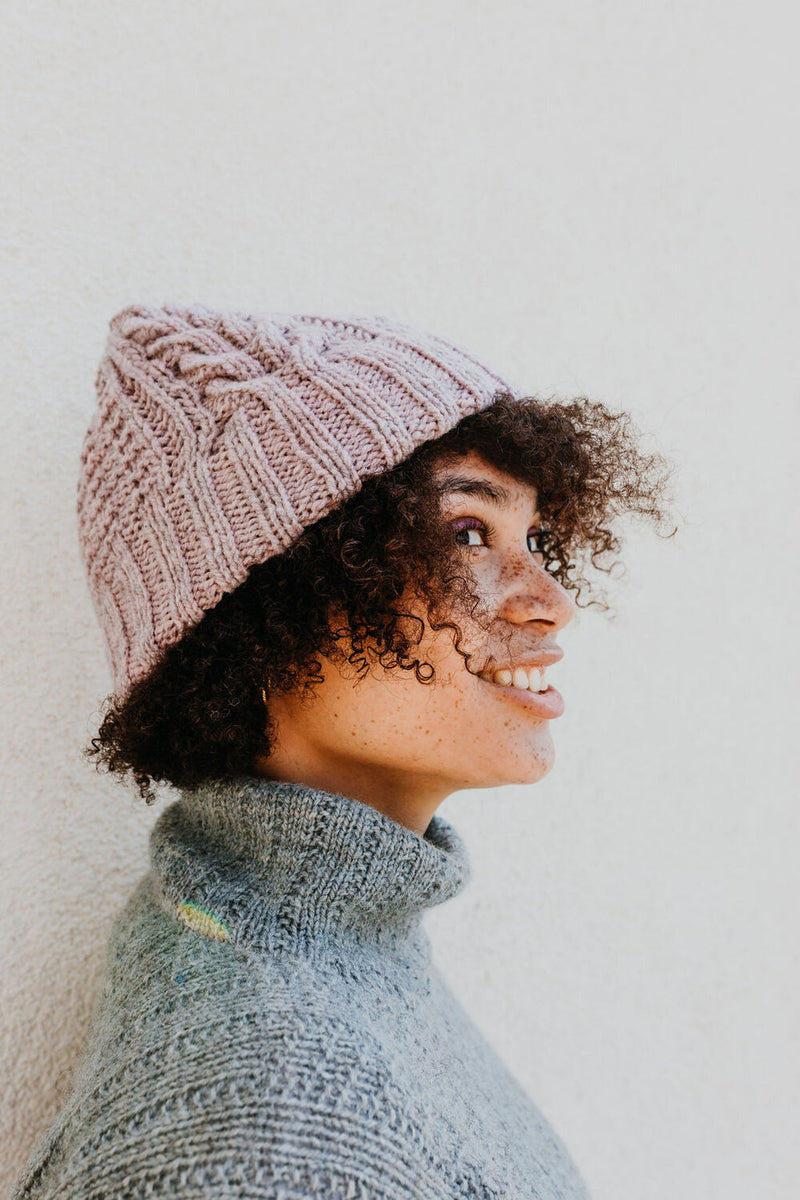 Pink thick beanie hat with cables and texture around the body