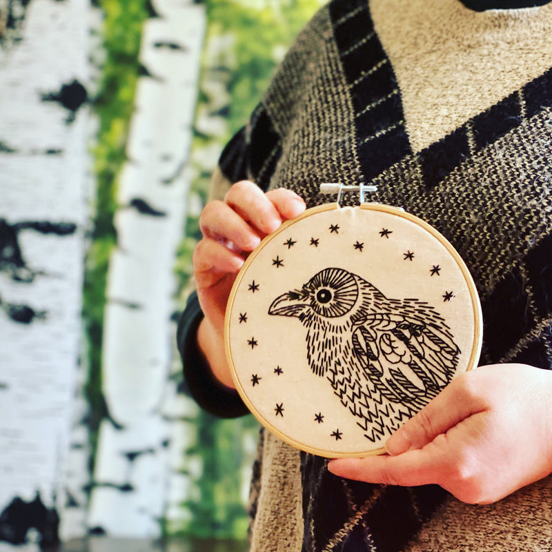 hands holding embroidery of a raven