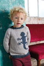 boy wearing a light grey knit sweater with an intarsia lizard and all ribbing in medium blue