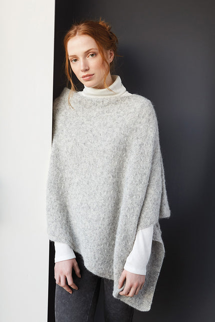woman wearing a light grey knit poncho