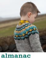 boy wearing a grey knit sweater with a mustard, navy, and turquoise patterned yoke