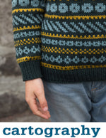 closeup of a navy knit sweater with light blue and mustard colourwork patterned stripes