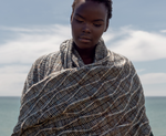 woman on a beach wearing a variegated blue, cream, and brown knit wrap
