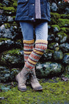 legs of a woman standing in front of a mossy stone wall wearing nordic colourwork striped leggings in bright colours