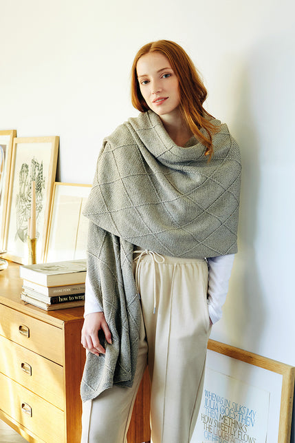 woman wearing a wide grey rectangular knit wrap with a textured diamond pattern