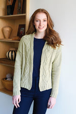 woman wearing a light green knit cardigan with cabled heart panels on the front sides
