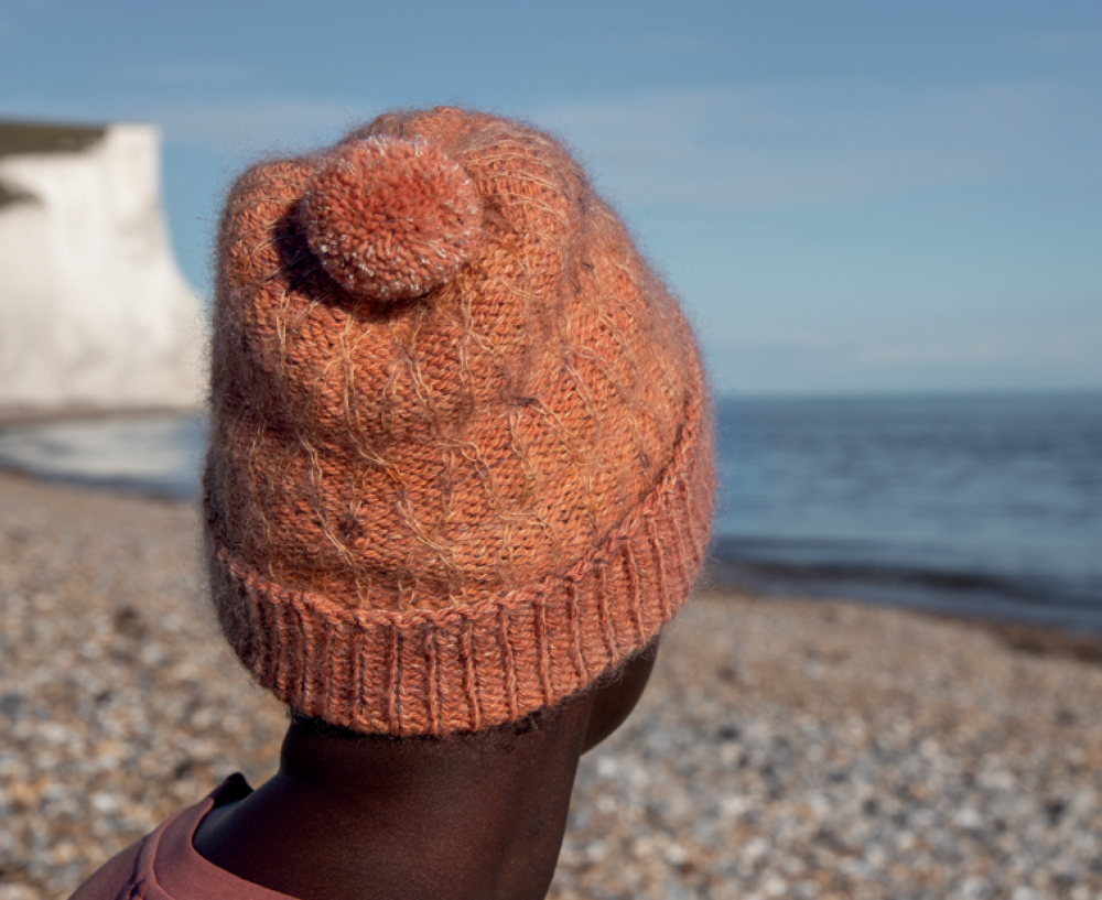 woman on a beach wearing a subtly cabled hat in orange
