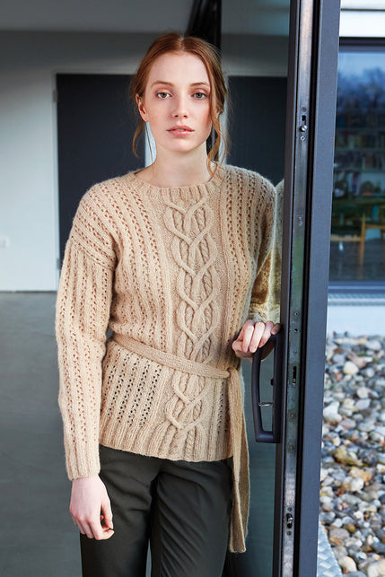 woman wearing a belted brown-cream knit sweater with horizontal eyelet stripes and a cable pattern in the centre front of the body.
