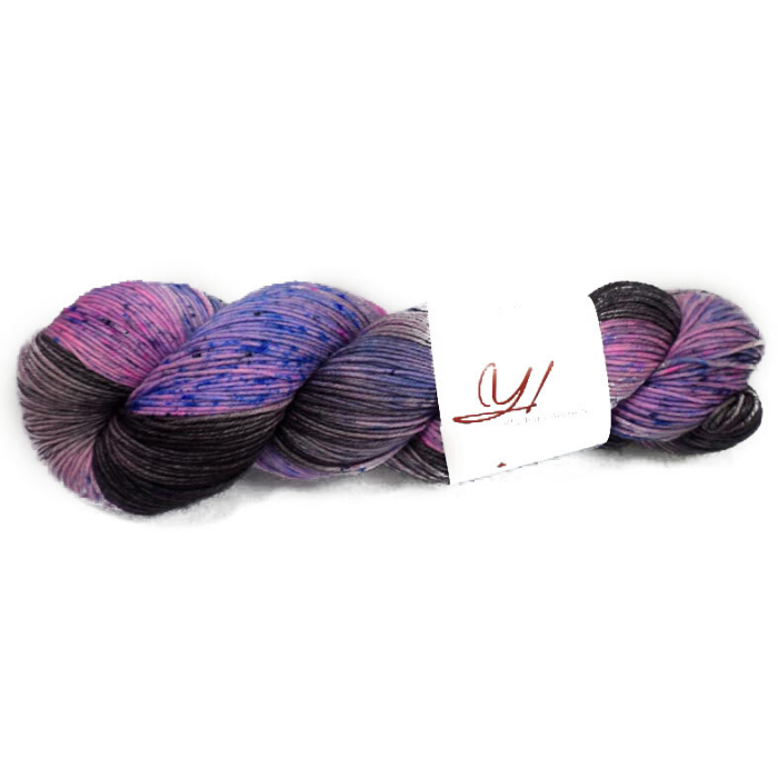 Light purple and black variegated skein of yarn with blue speckles
