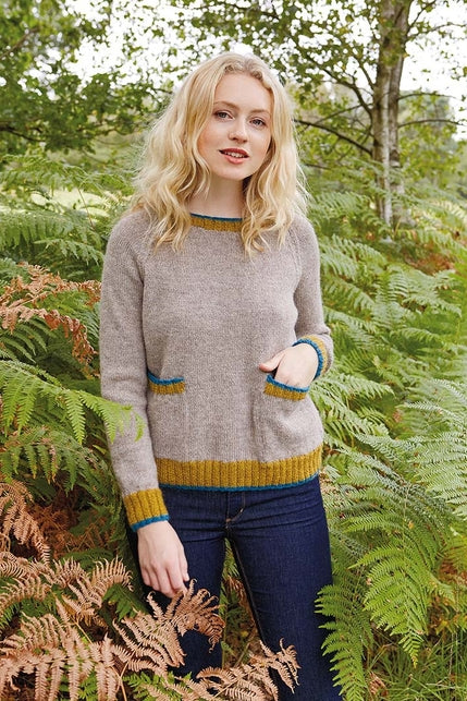 woman wearing a brown-grey knit sweater with pockets trimmed in mustard and bright blue ribbing