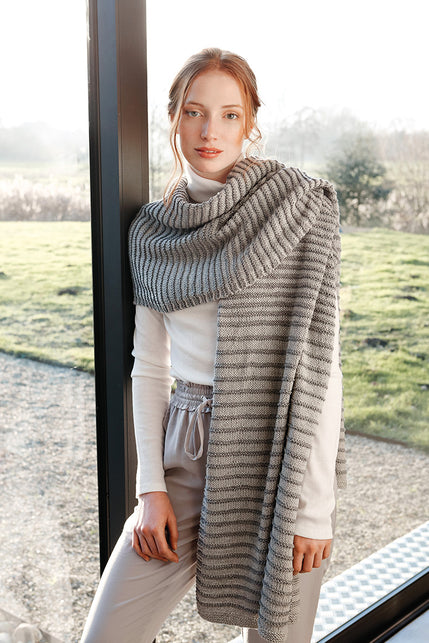 woman wearing a wide grey rectangular knit wrap with textured stripes
