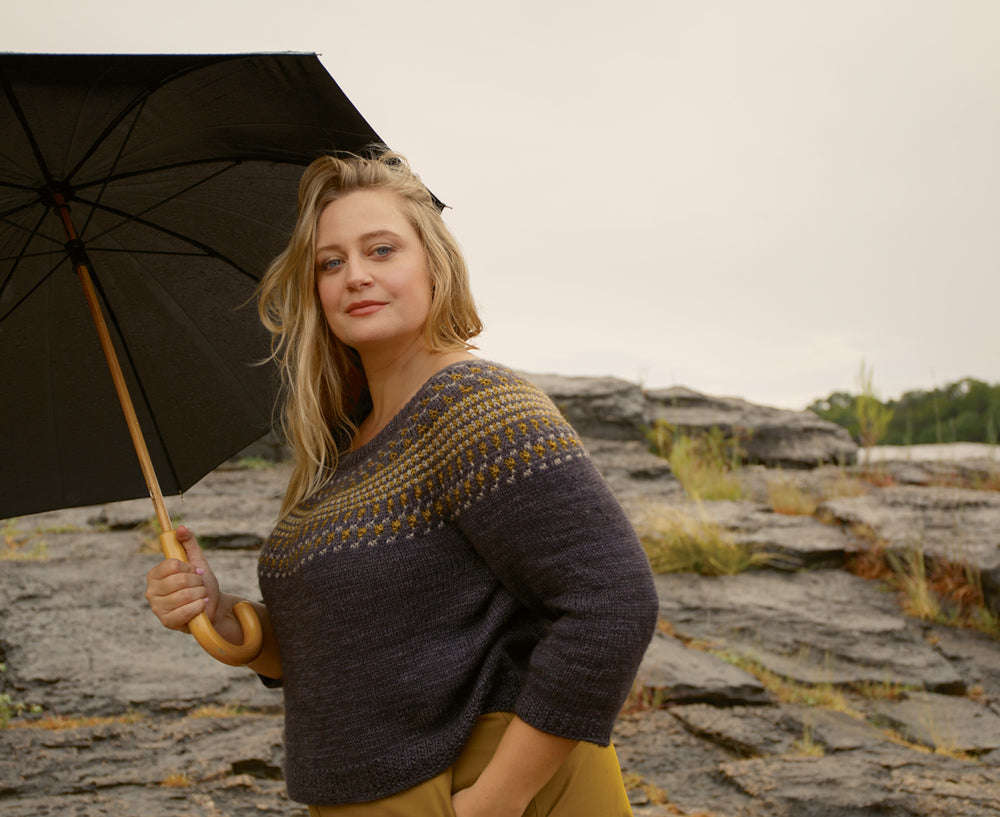 woman carrying an umbrella wearing a grey sweater with a yellow and white colourwork yoke