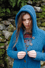 woman wearing a blue cabled hooded cardigan standing in front of a mossy stone wall