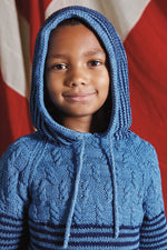 boy wearing a hooded knit sweater in light blue with cables on the yoke and navy stripes on the body and hood