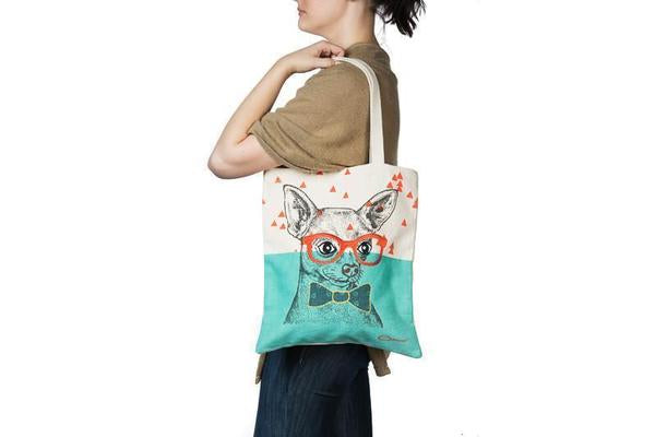 woman carrying a tote bag featuring a print of a dog wearing glasses