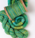 kiwi bobbin holding spun green and yellow fibre, sitting beside a skein of yarn plied from the same fibre and a rolag of roving from the same fibre.