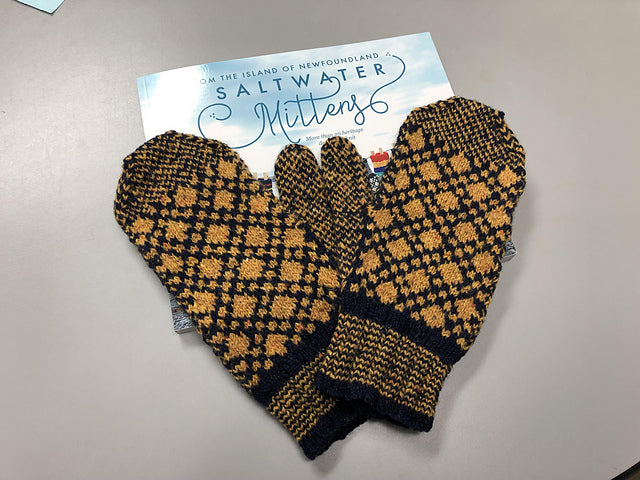 Saltwater mittens book sitting on a table with mustard and black colourwork mittens sitting on top.