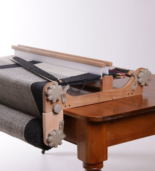 rigid heddle loom with a freedom roller attached sitting on a table.