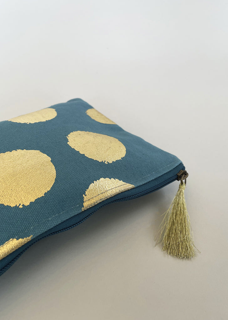 Close up detail of gold tassel on zip.