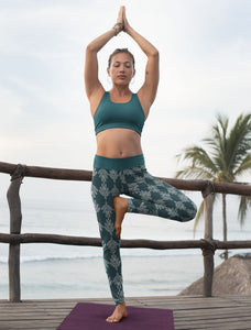 Woman Wearing Pure Free Spirit Eco Friendly Sustainable Yoga Capris Pants Leggings in Teal Feather Print Athletic Streetwear Gym Loungewear Athleisure Compression fit