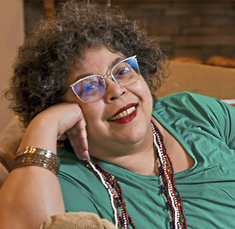 Iya C, a light skinned short curly fro woman, smiles warmly into the camera.