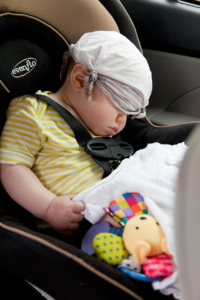Image of a Baby Asleep In Car Seat with Hankie on Their Head