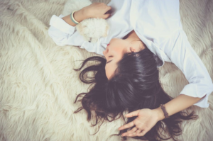 Image of a women on her back asleep with her arm above her head