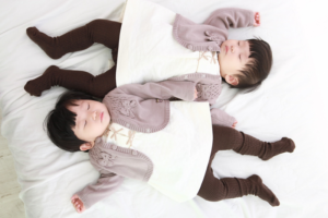 Image of twins dressed in matching outfits asleep