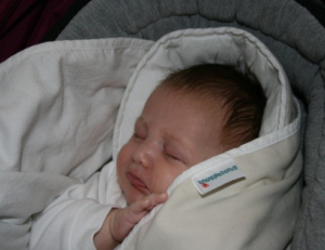 Snugglebundl - Importance of Supporting a Baby's Head Blog - Image of a baby asleep wrapped in the Snugglebundl