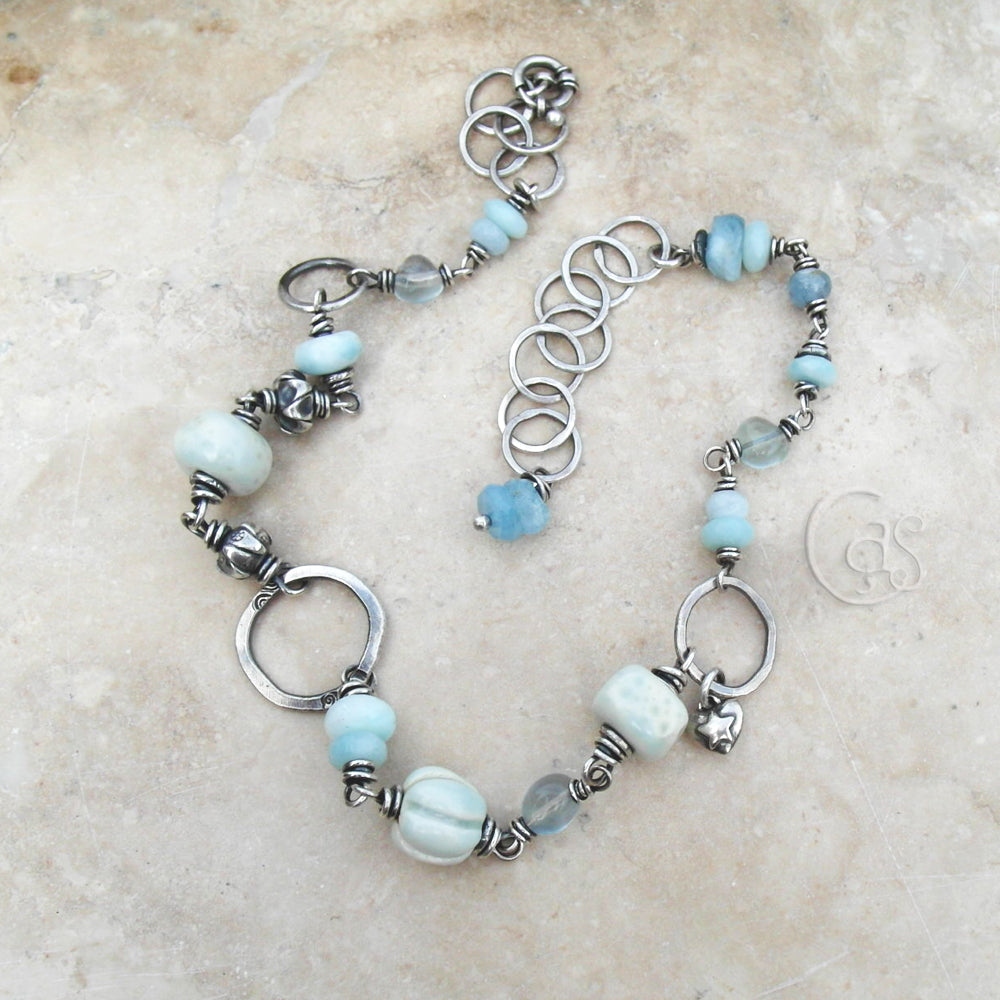 This necklace features an eclectic mix of beads including handcrafted porcelain, handcrafted fine silver, Bali Silver, Hill Tribe Silver, Aquamarine gemstones, Fluorite gemstones, and more!  Each section has been lovingly wrapped with pure silver wire. Each bead hand picked for it's size, and beauty to fit into the mix.  Rings are made of pure, raw silver. Hand forged and gently hammered. Just off center I added a small puffy heart charm of .925 sterling silver with a star motif.