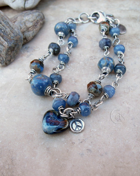 This blue gemstone bracelet is handcrafted by Cindy's Art & Soul Jewelry. Sterling Silver wire wrapped gemstones include blue kyanite, and blue Spectrolite. The center charm is a handmade porcelain heart and peace sign.