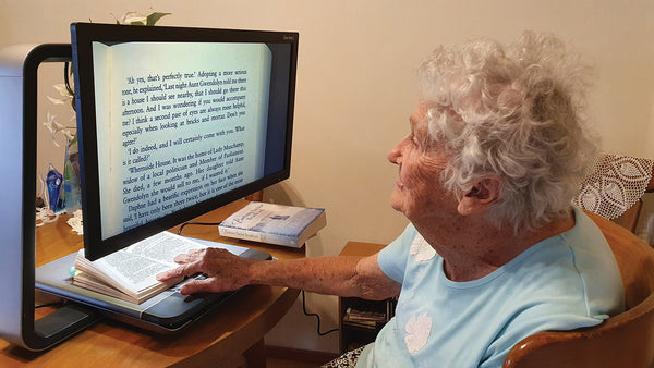 Elderly Lady using Quantum RLV Devices to enlarge text in a book and read