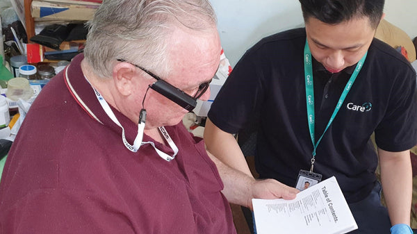 Image shows Gary sitting with Occupational Therapist, Rafael Lau and using the OrCam MyEye Pro to read a document aloud.