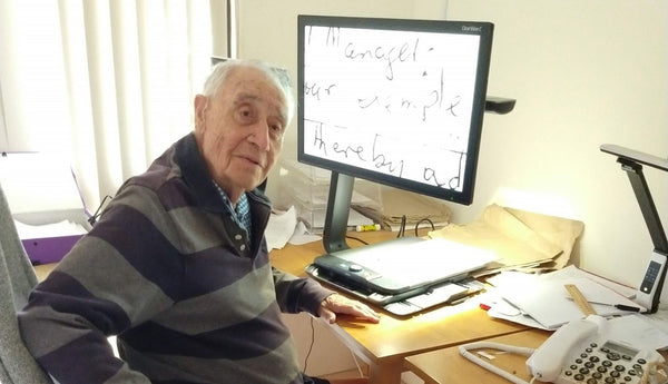Image shows Jack sitting at his desk writing with the help of his ClearView  Widevision magnifier.
