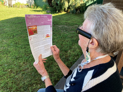 Photo of Marion using OrCam to read the village newsletter.